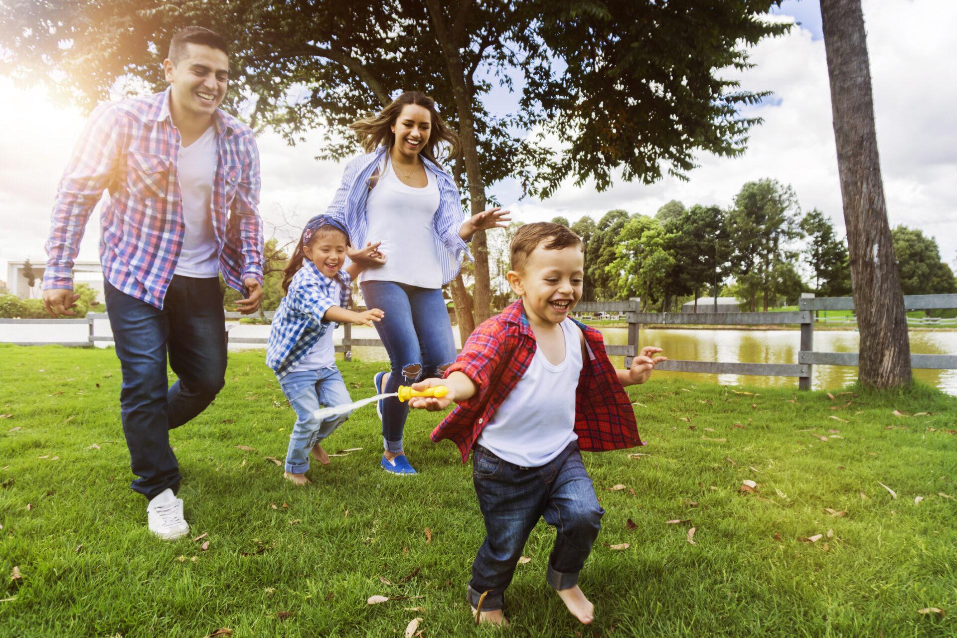 Happy family running around the park